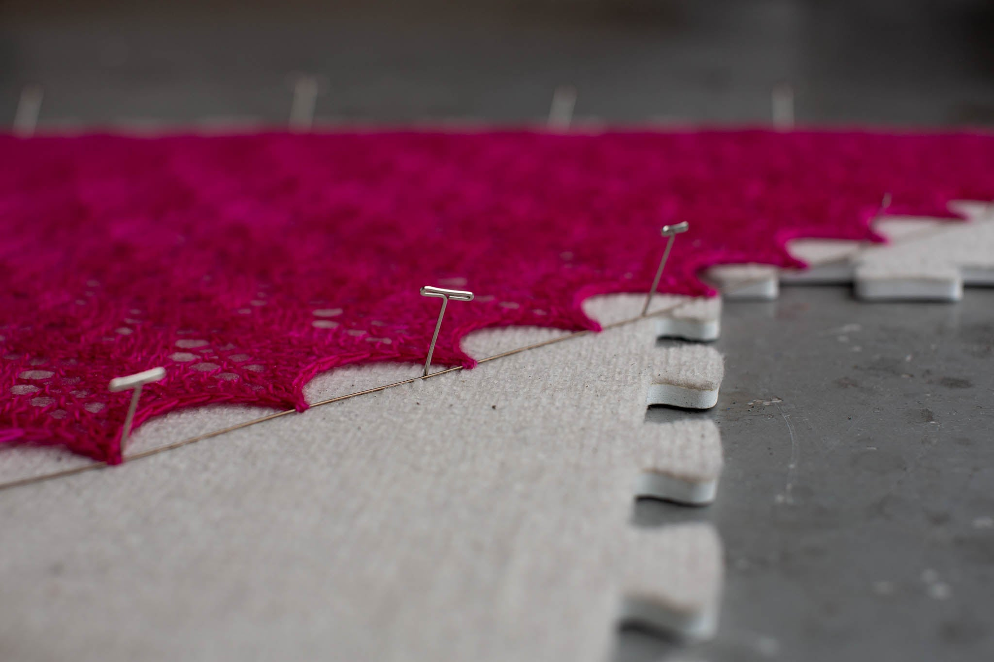 A close up of the scalloped edges of a pink shawl, being held by blocking wires and pinned to a blocking mat.