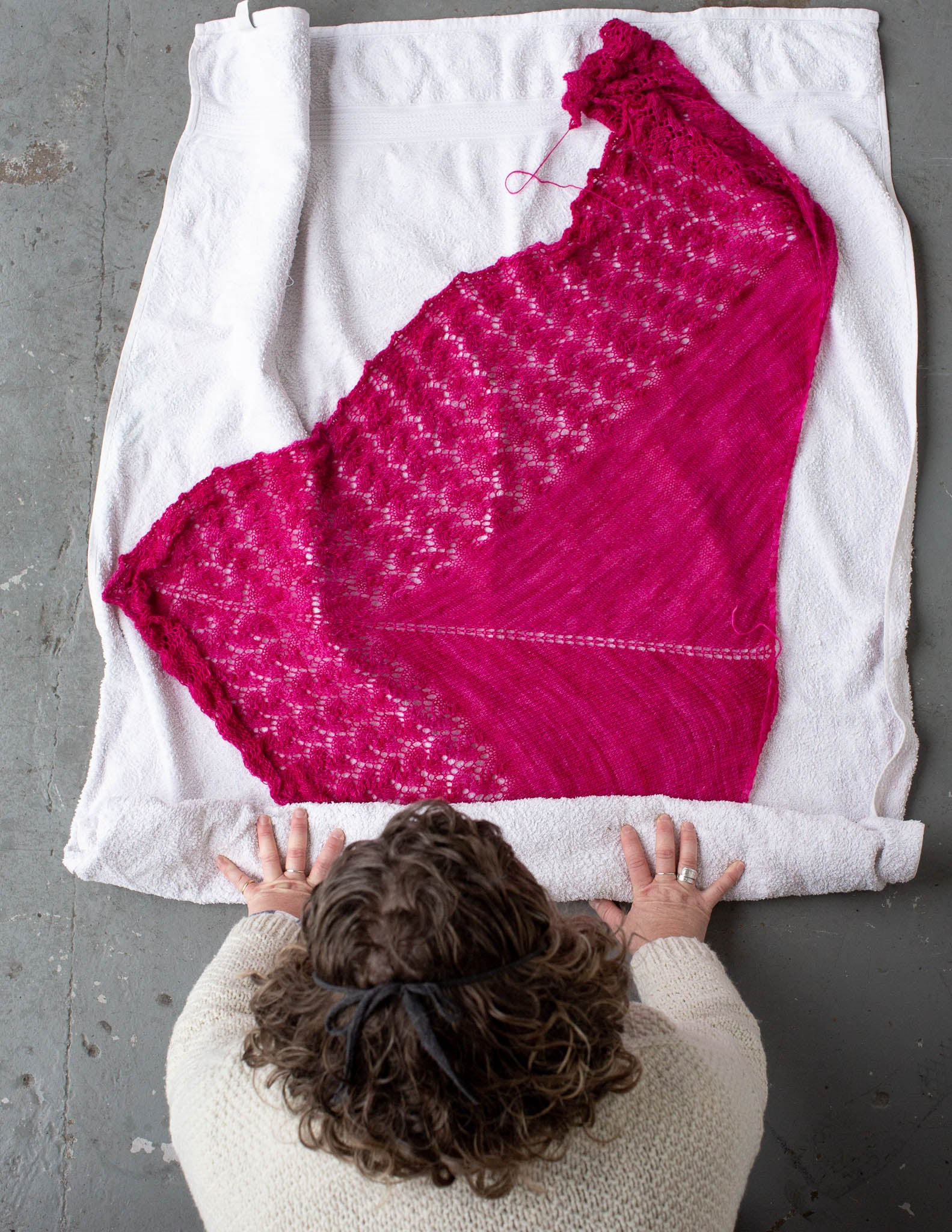 A pink shawl has been laid out on a white towel, on a grey floor. The towel is being rolled up from the bottom with the shawl enclosed inside by a white woman at the bottom of the picture. She has dark curly hair and wears a white sweater.