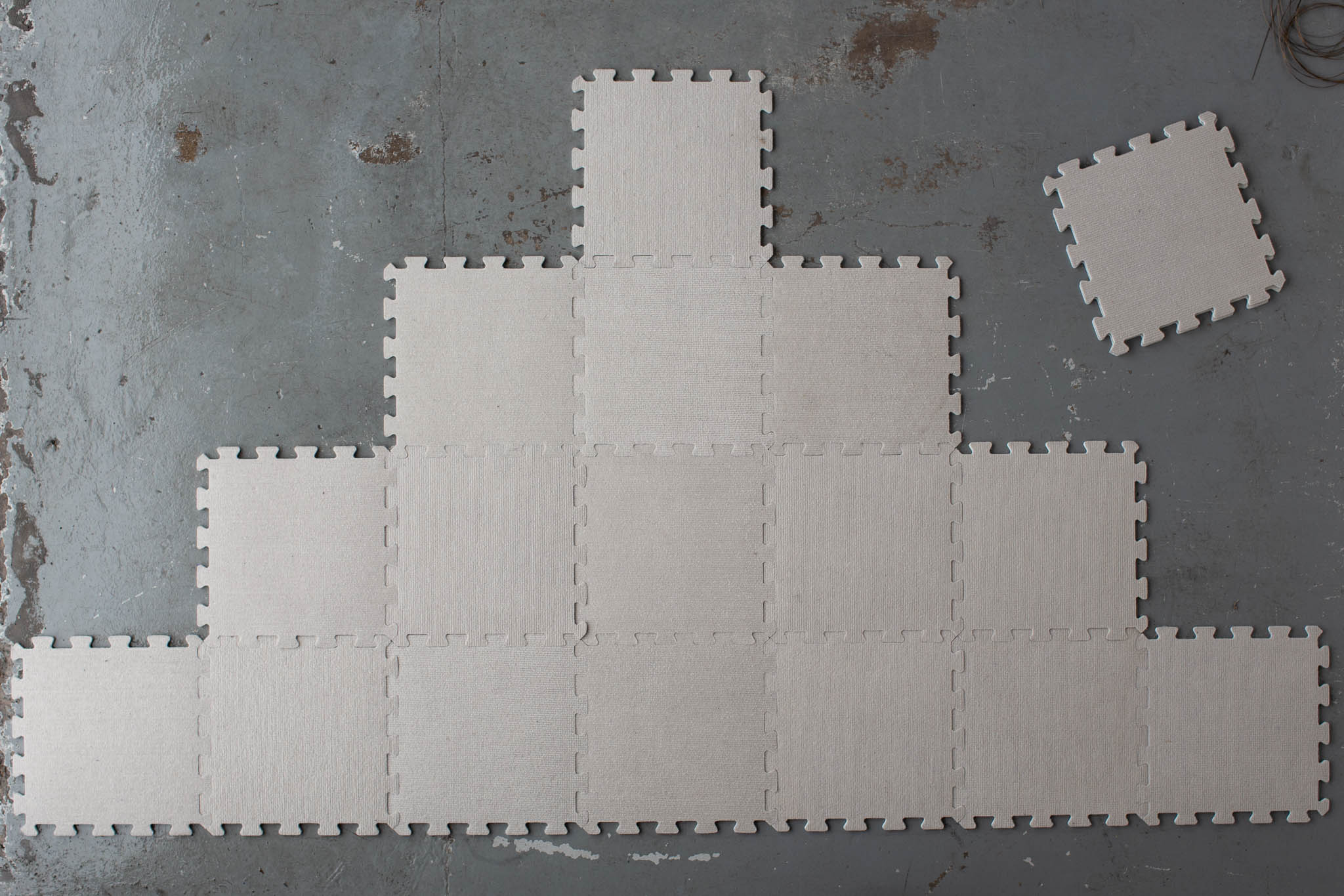 White blocking mats are arranged on a flat grey surface in a pyramid shape, with 7 on the lower level, 5 above that, then 3, then 1. A spare blocking mat lies to the right side.