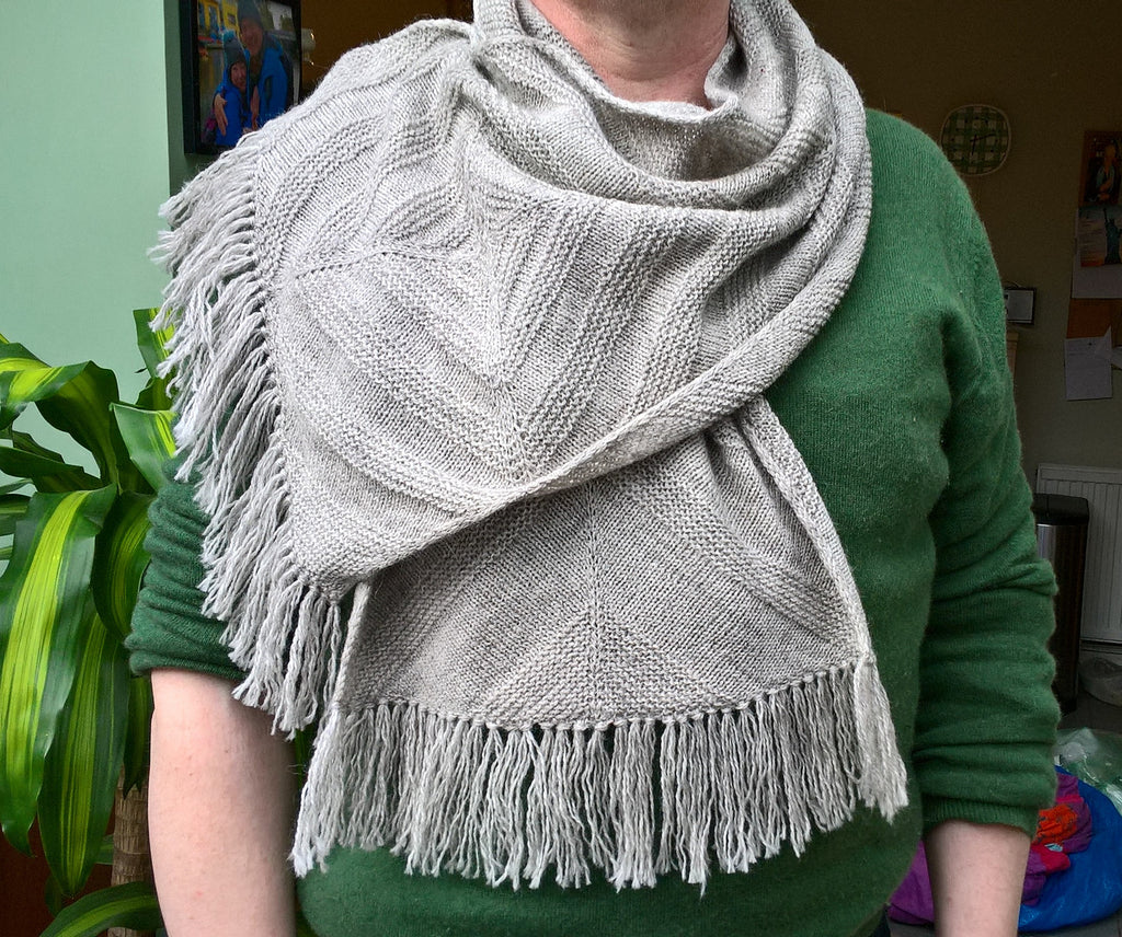 Close up of a man wearing the phobos  scarf with both ends draped towards the front, the ends feature a simple knotted on fringe in the same yarn