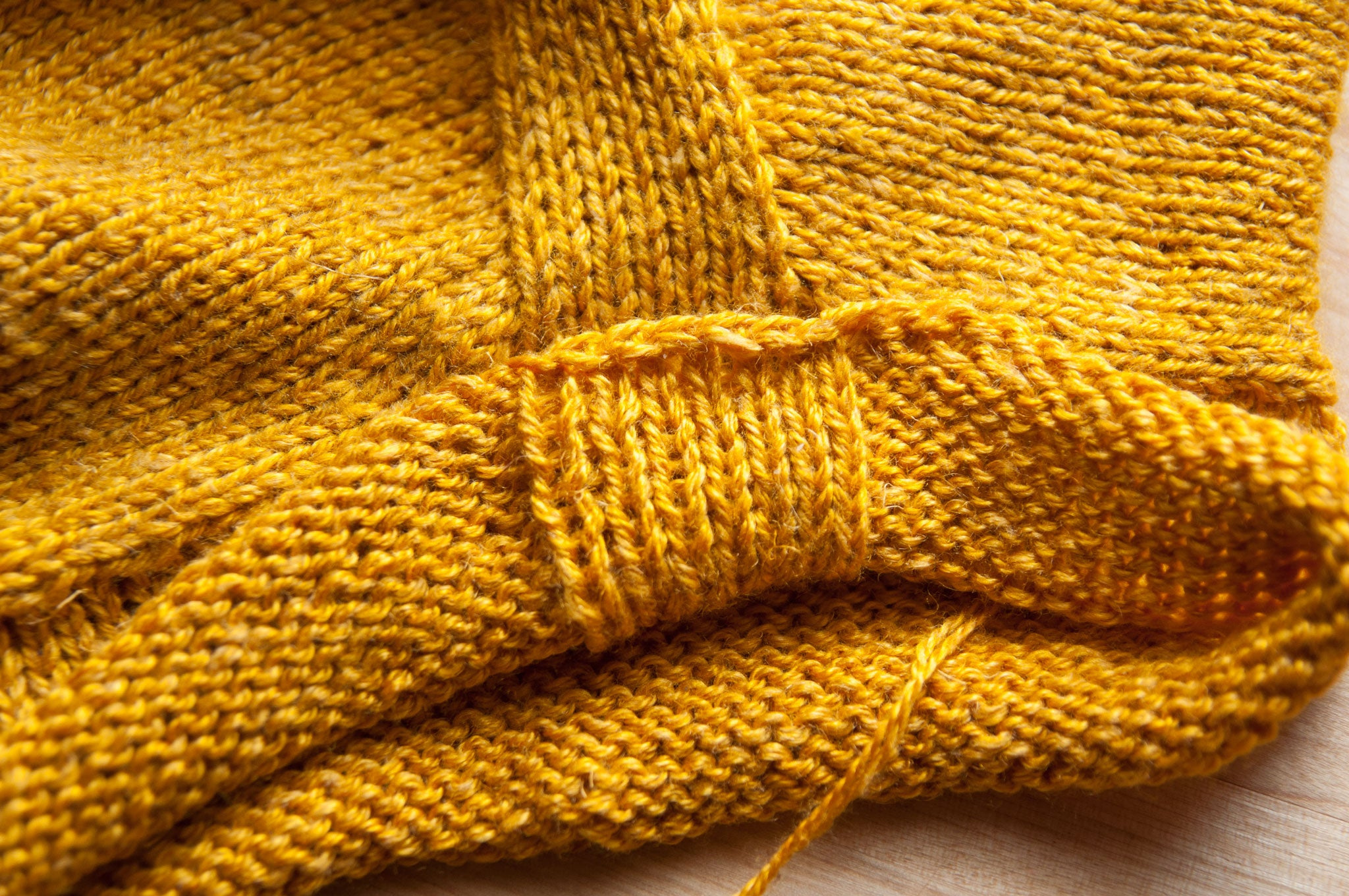 Fold the sleeve cuff up so there is a narrow strip of stockinette in the center.