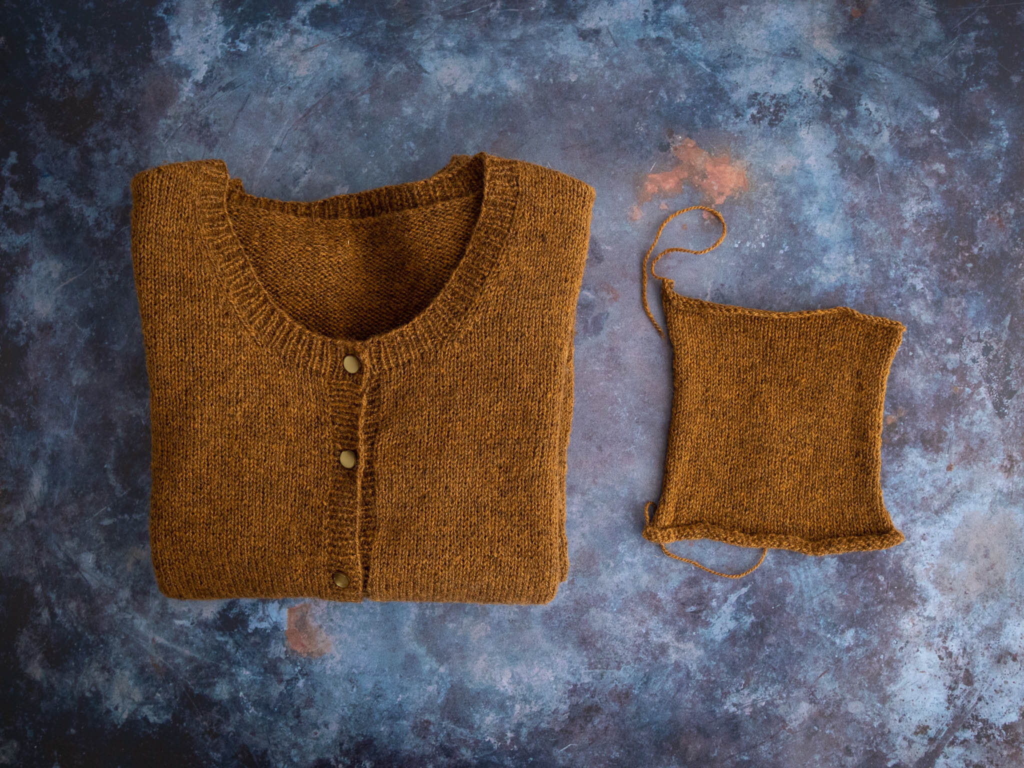 A honey brown cardigan with round neck is folded and lies on a moody dark blue flat surface. To the right of the sweater is a small swatch in the same yarn.