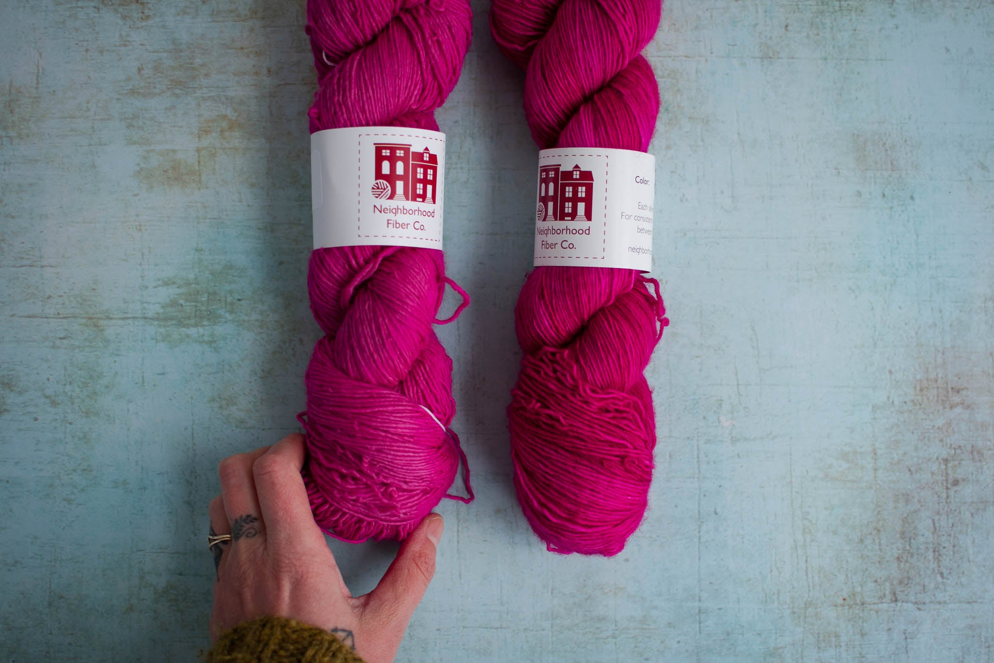 Two skeins of pink yarn, with a hand touching the bottom of the skein on the left. The right skein is darker and more saturated.