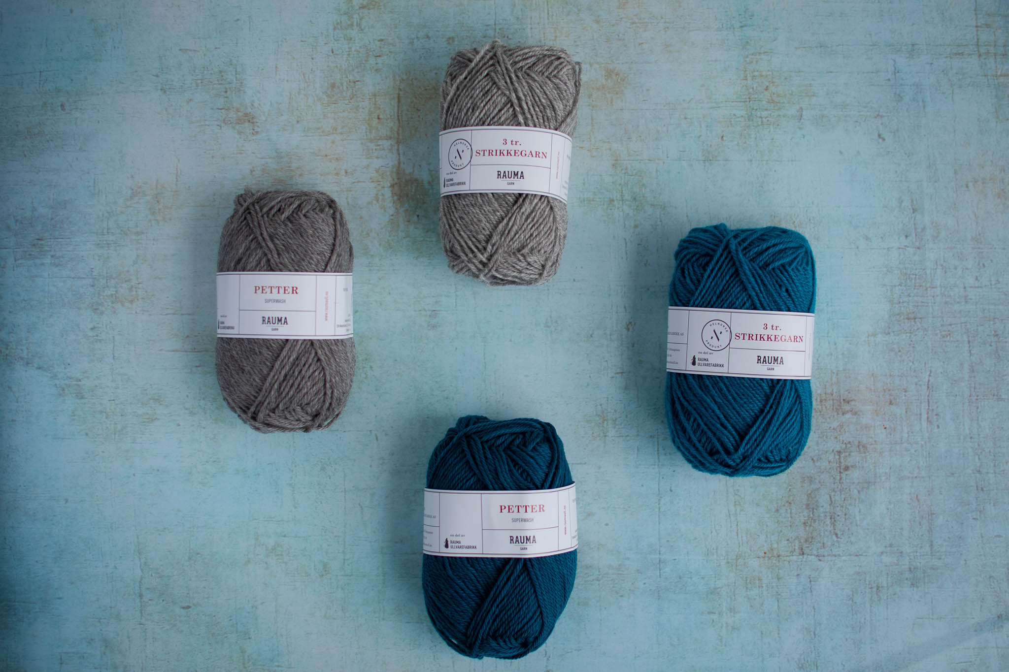 Four balls of yarn arranged on a flat surface, two are grey and two are teal but each of one is slightly darker than the other.