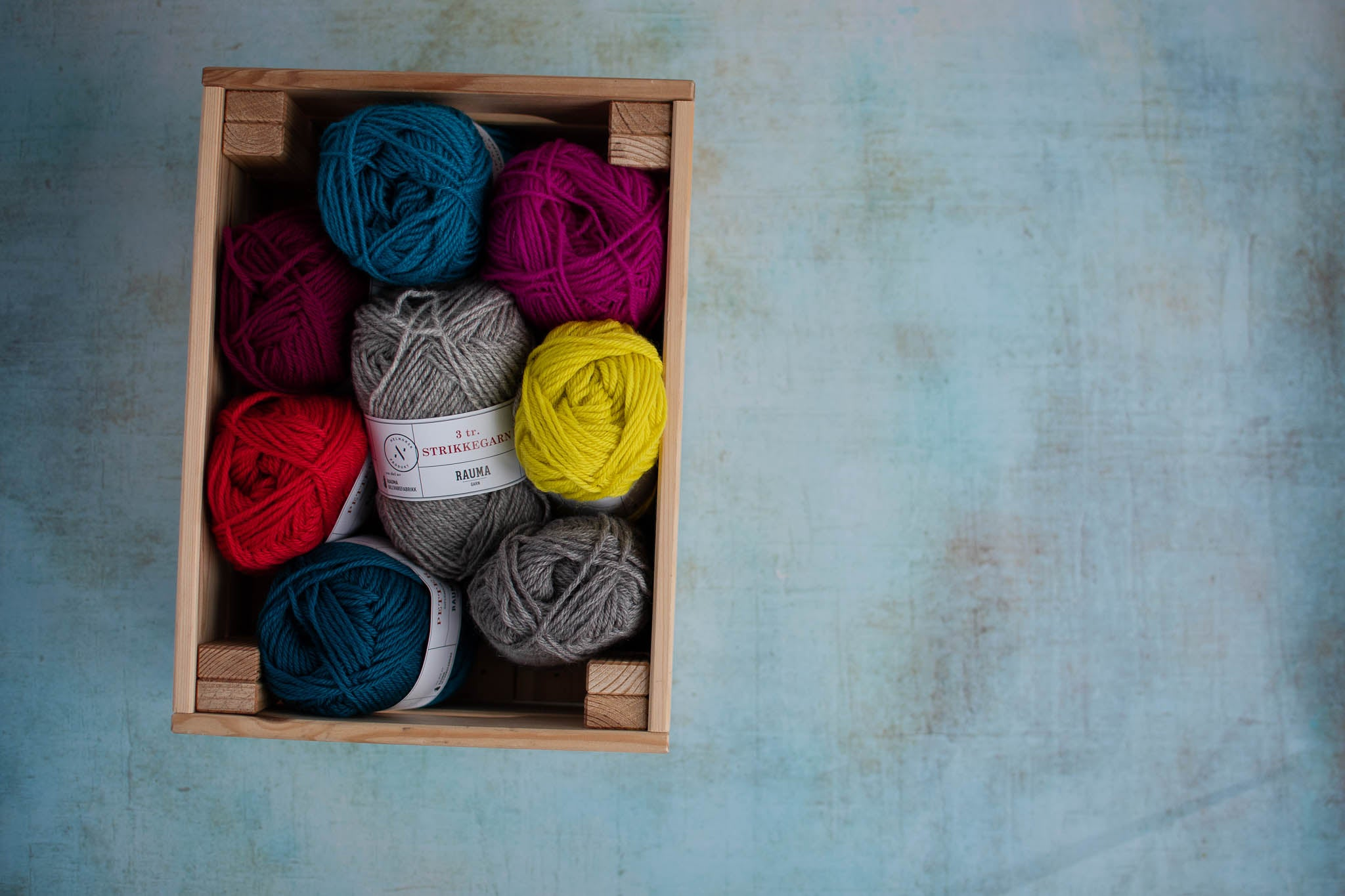 A small wooden box holds balls of yarn in a variety of colours. The box is placed to the left of the image.