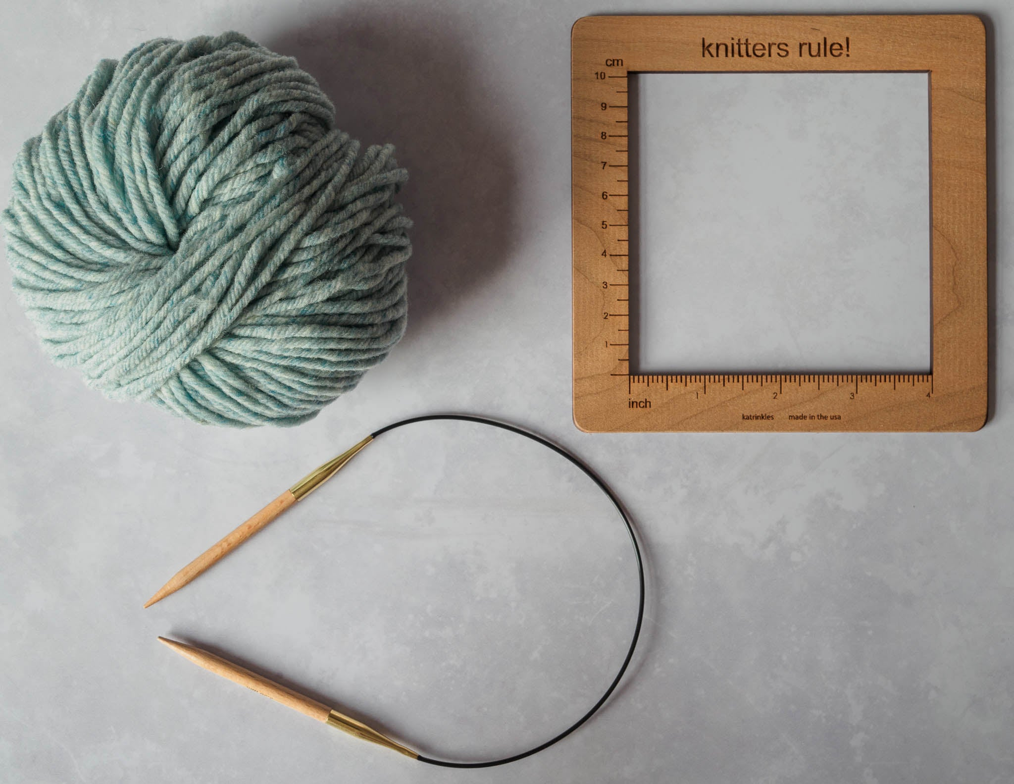 A ball of pale blue yarn, circular knitting needles and a wooden swatch measurement tool.