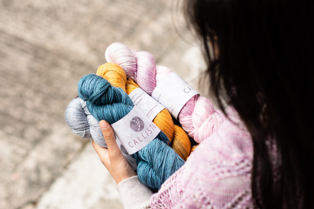 image of skeins of pink, blue, gold and purple wool/silk yarn being held by a dark haired woman