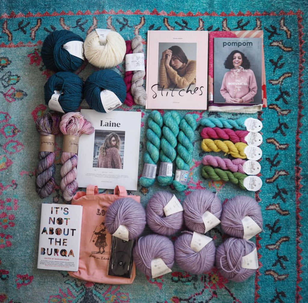 Thebrightblooms's EYF Purchases: Balls and skeins of yarn arranged in a blue patterned carpet. Copies of Pompom, Laine, Stitches and It's Not About the Burqa are arranged among the yarn.