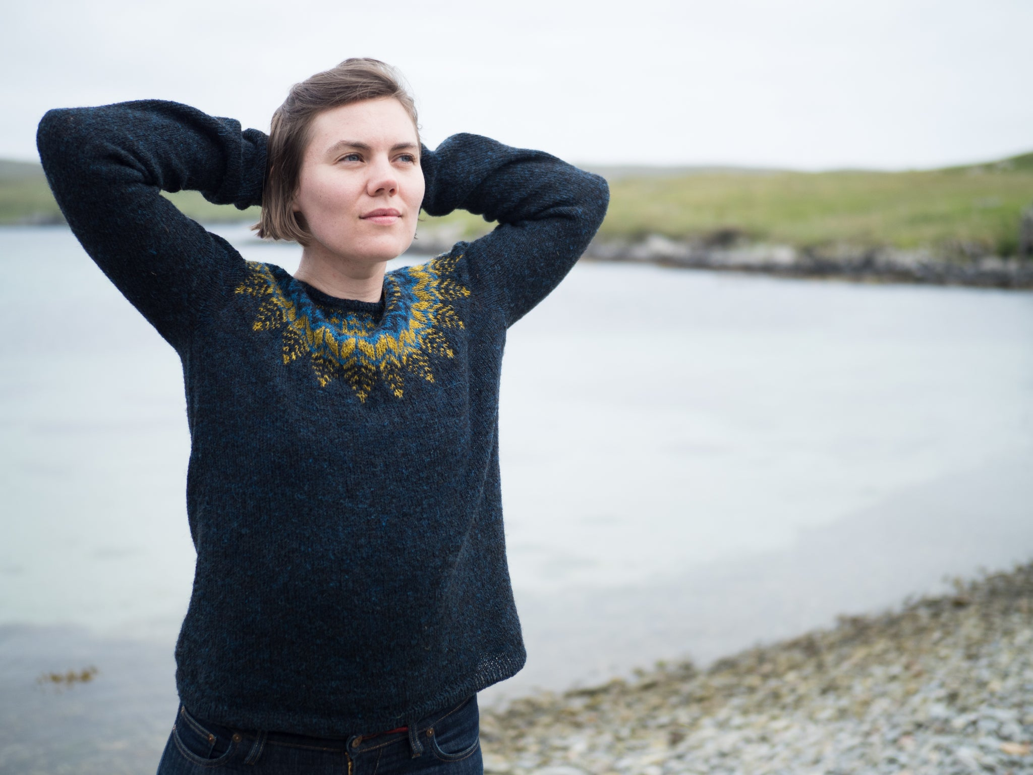 White woman wearing a dark blue sweater with a yellow and light blue patterned yoke, standing on a pebble beach with her hands behind her head