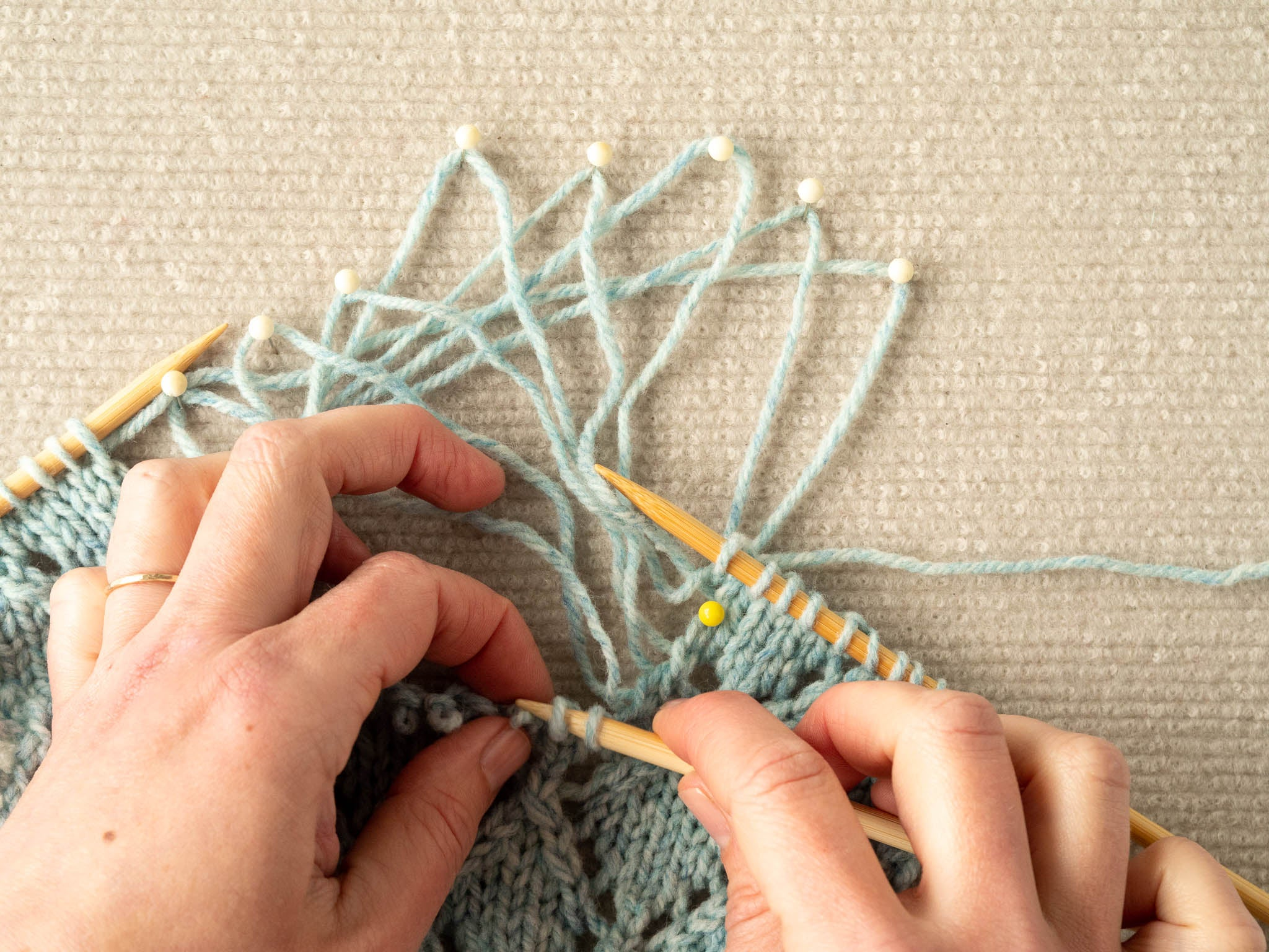 photo showing several unravelled strands of a swatch pinned out on a blocking mat