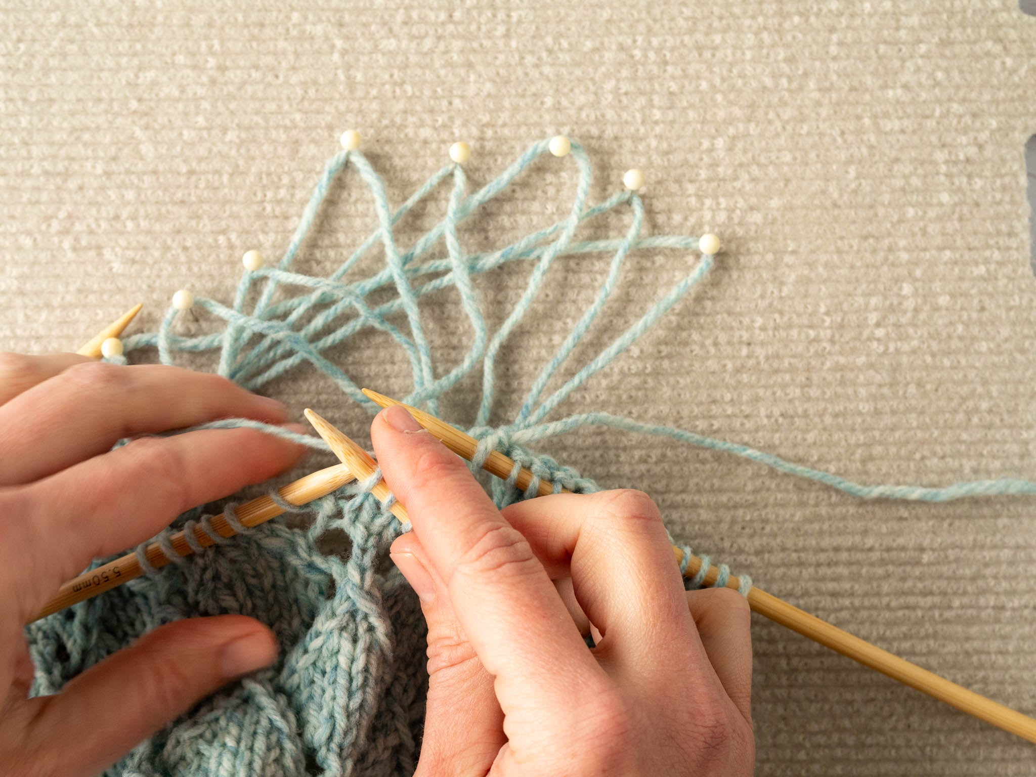 photo showing unravelled strands pulled out, while the section is being reknit on dpns