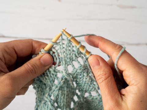 photo showing the left needle tip inserted into one stitch of a decrease