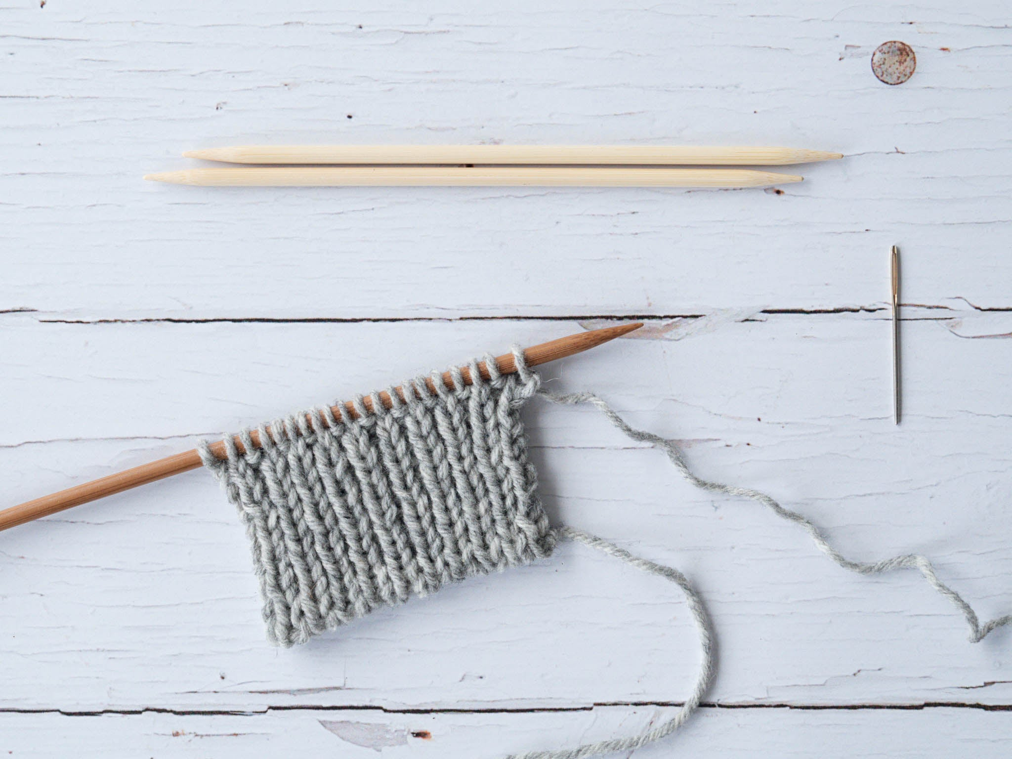 ribbed swatch on a wooden needle with two dpns and a darning needle