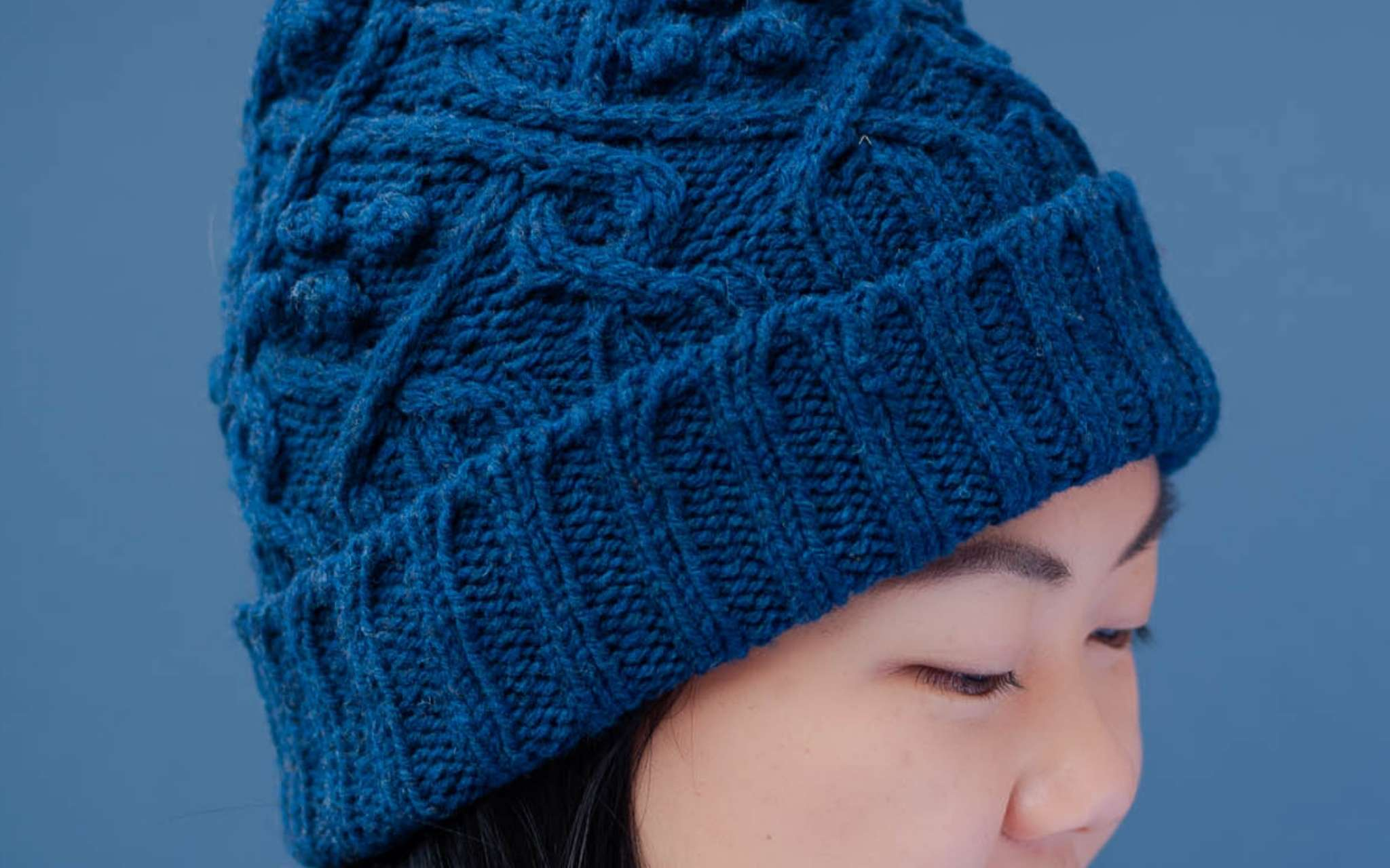 a close up of the brim of a blue cabled hat with a ribbed, folded edge