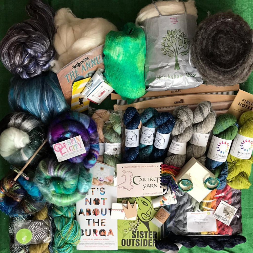 Image of purchases with fibre at the top and down the left hand side, a spindle on top of some of the fibre, then some skeins of yarn in the middle right and It's Not About the Burqa and Sister Outsider visible at the bottom