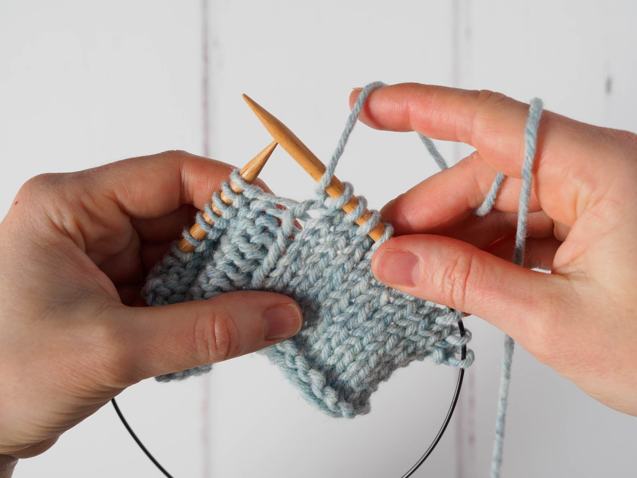 A small grey swatch is on the needles, with purl stitches showing to the left and knit stitches to the right. The working yarn has been brought to the front between the needles.