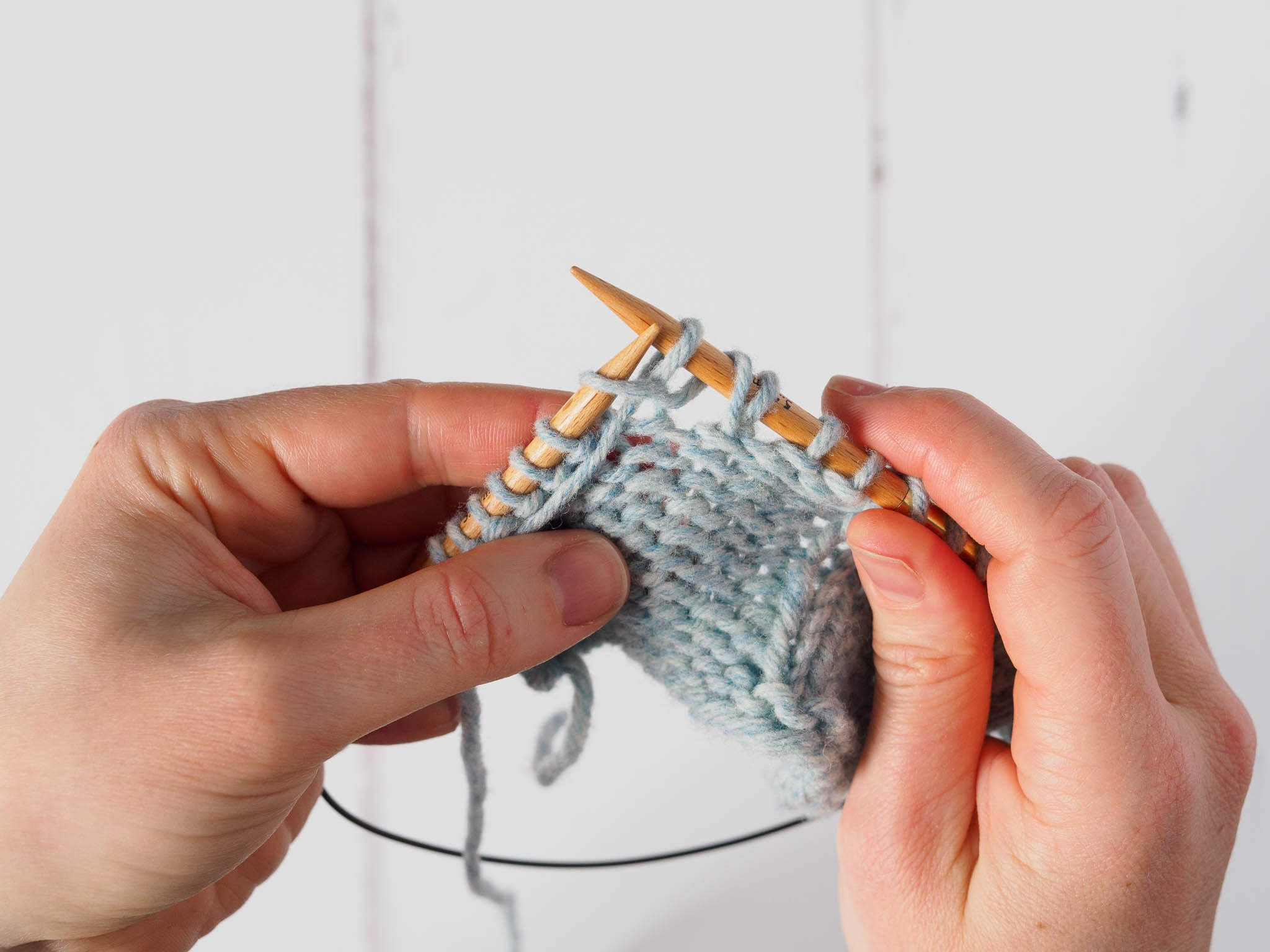 A small grey swatch where a yarn over has been formed on the right needle, and the next stitch is now being purled.