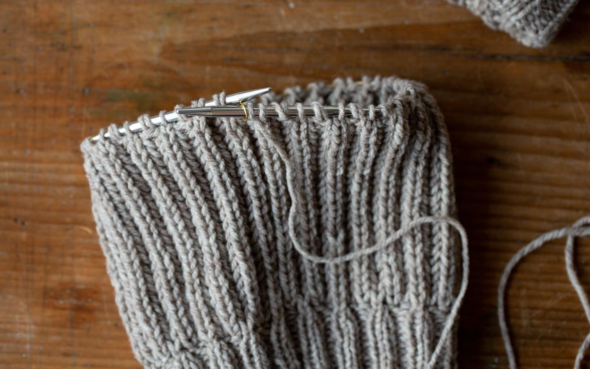 A hat in progress knitted in a brioche stitch, showing the yarn overs created nestled beside their corresponding stitches on the needle.