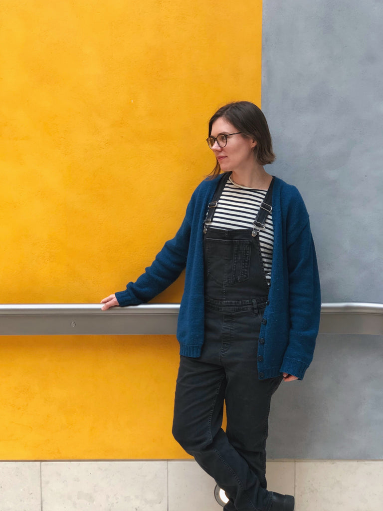Woman with pale skin wearing dark overalls, a striped shirt and a blue oversized Wardie against a yellow and grey wall