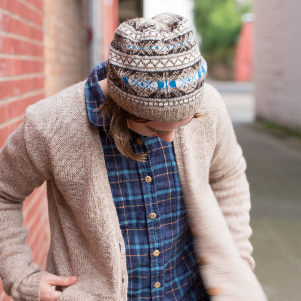 Ysolda, a white woman with chin-length brown hair, stands next to a brick wall looking at the ground. She is wearing a brown and grey Fair Isle hat with a blue accent detail, a blue plaid shirt and brown cardigan