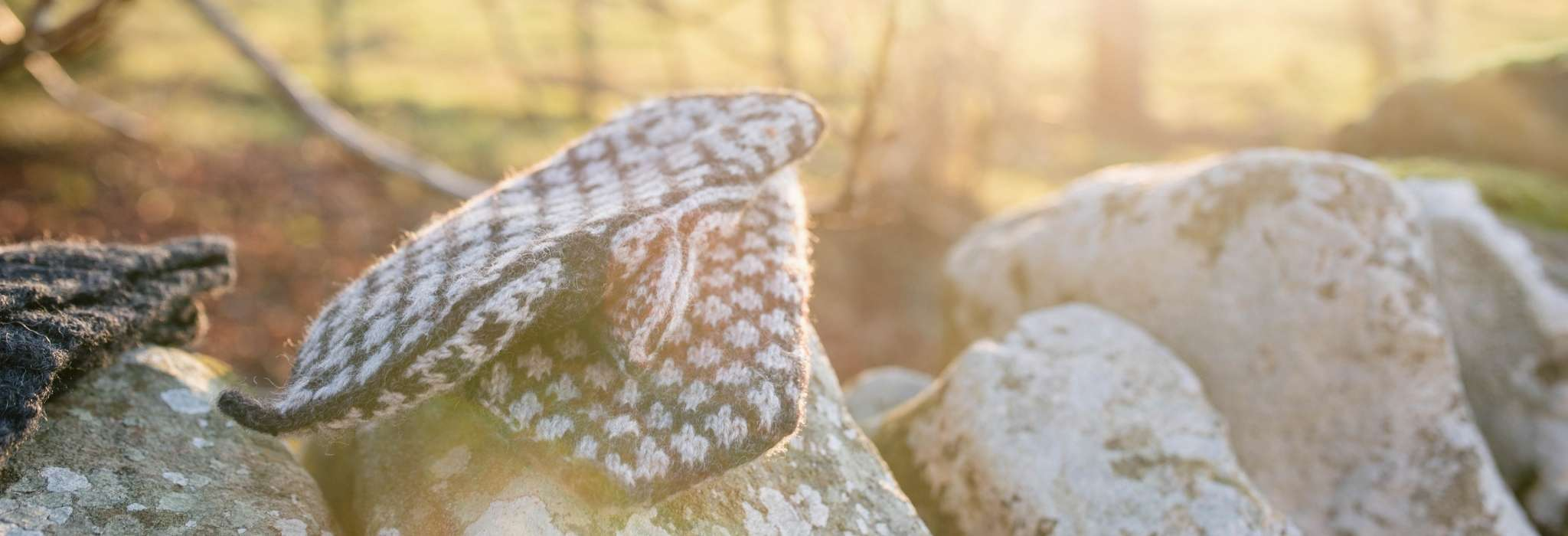 A pair of dark and cream colourwork mittens lie on top of each other, overlapping. They are draped on the top of a stone wall, with trees and a sunset out of focus behind.