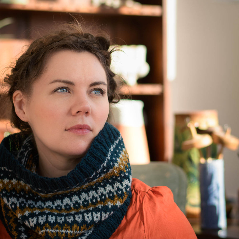 Ysolda looks to the side wearing an orange shirt and a large stranded colourwork cowl. The cowl is 3 colours in teal, light blue, and olive