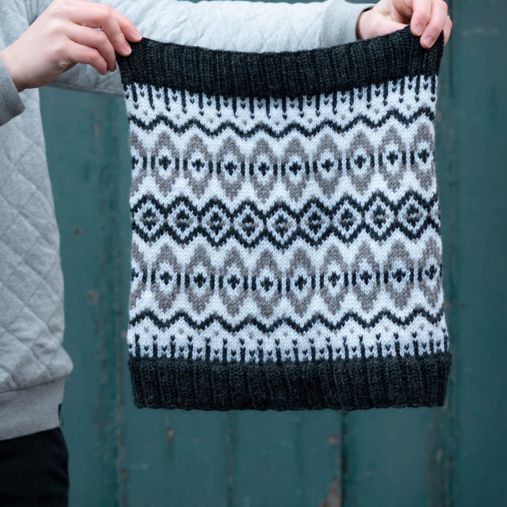 Two white hands hold a black, white, and grey cowl outstretched. the cowl is stranded colourwork with strong oval and diamond motifs