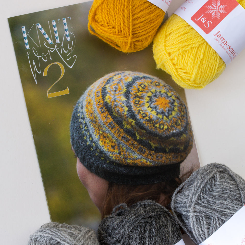 Saudade printed pattern flat on a white table, surrounded by 5 balls of wool in grey and yellow