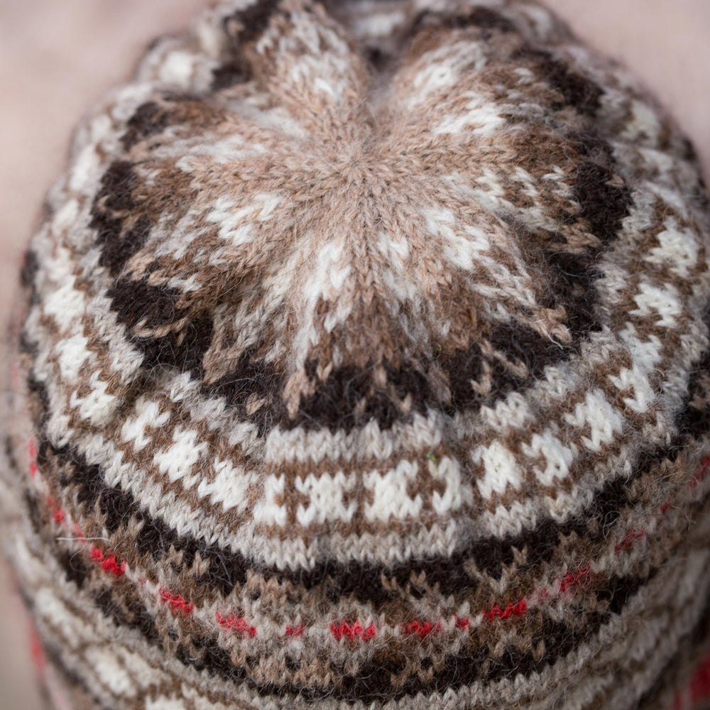 A close-up image of the top of a classic fair isle hat in neutral colours with a red accent stripe