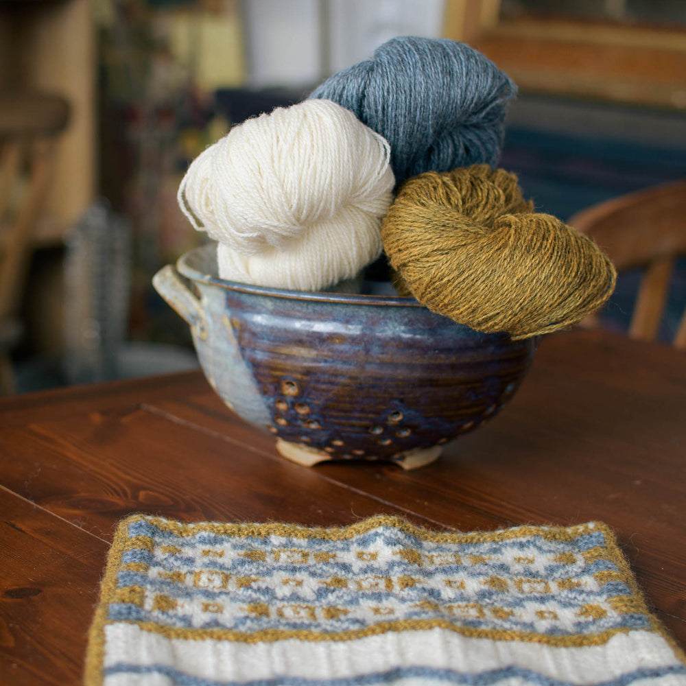 A ceramic bowl holds three skeins of yarn - white, gold, and blue. a stranded colourwork swatch in the same colours lays on the table in front.