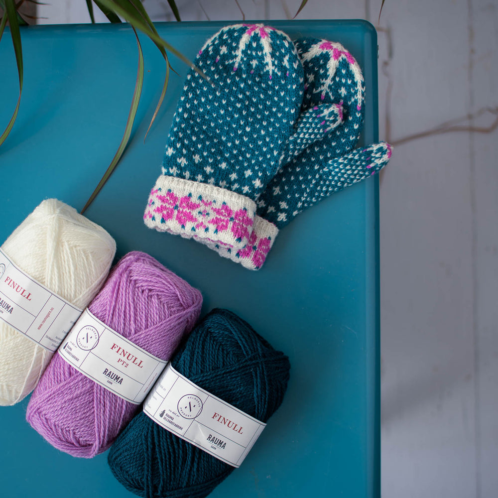 overhead view of stranded colourwork mittens and three balls of yarn in purple, teal, and white. sitting on a blue table