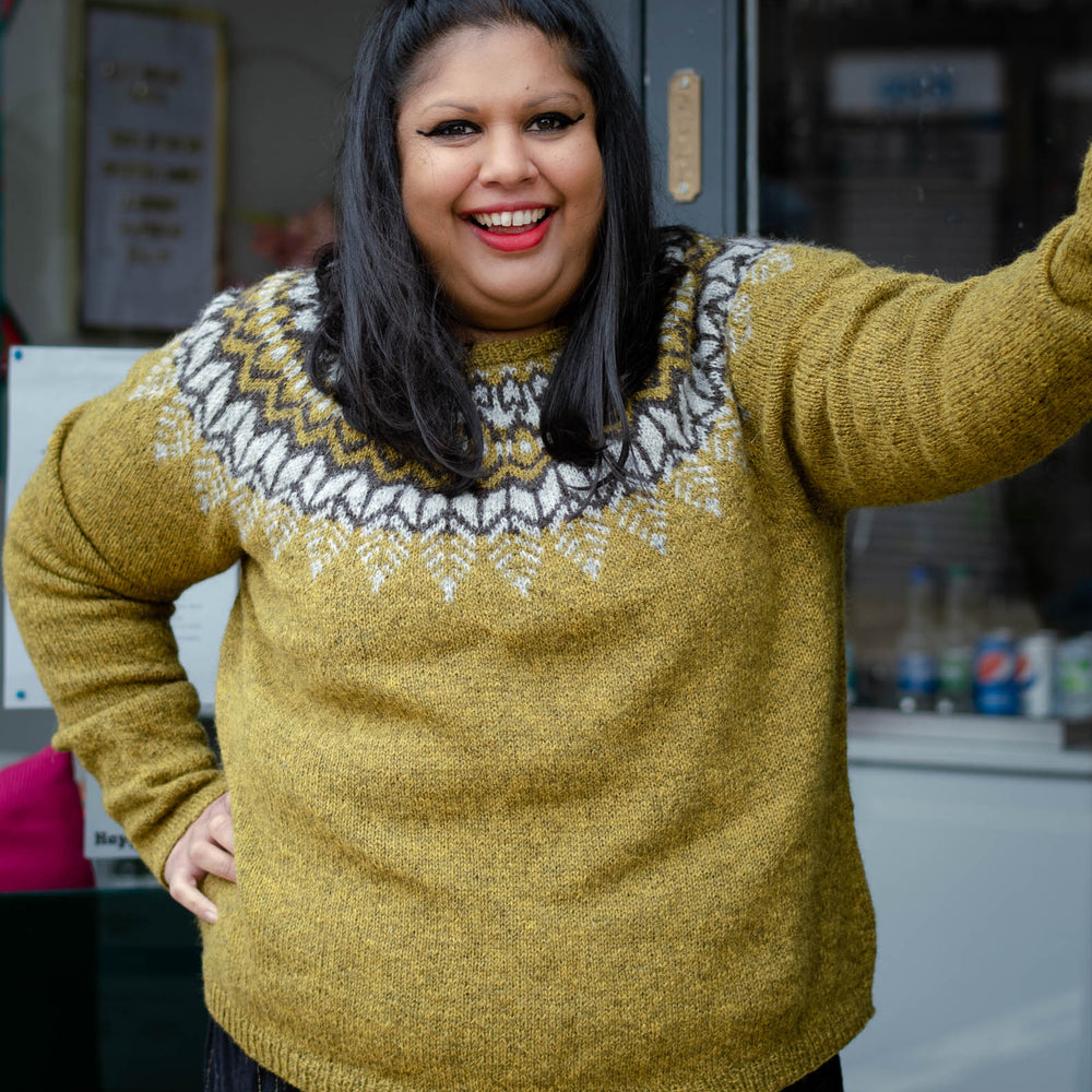 A south asian woman with mid length dark hair stands in a doorway looking towards the right of the frame. She is wearing  an earthy green knit sweater with a dark brown and light grey colourwork yoke.