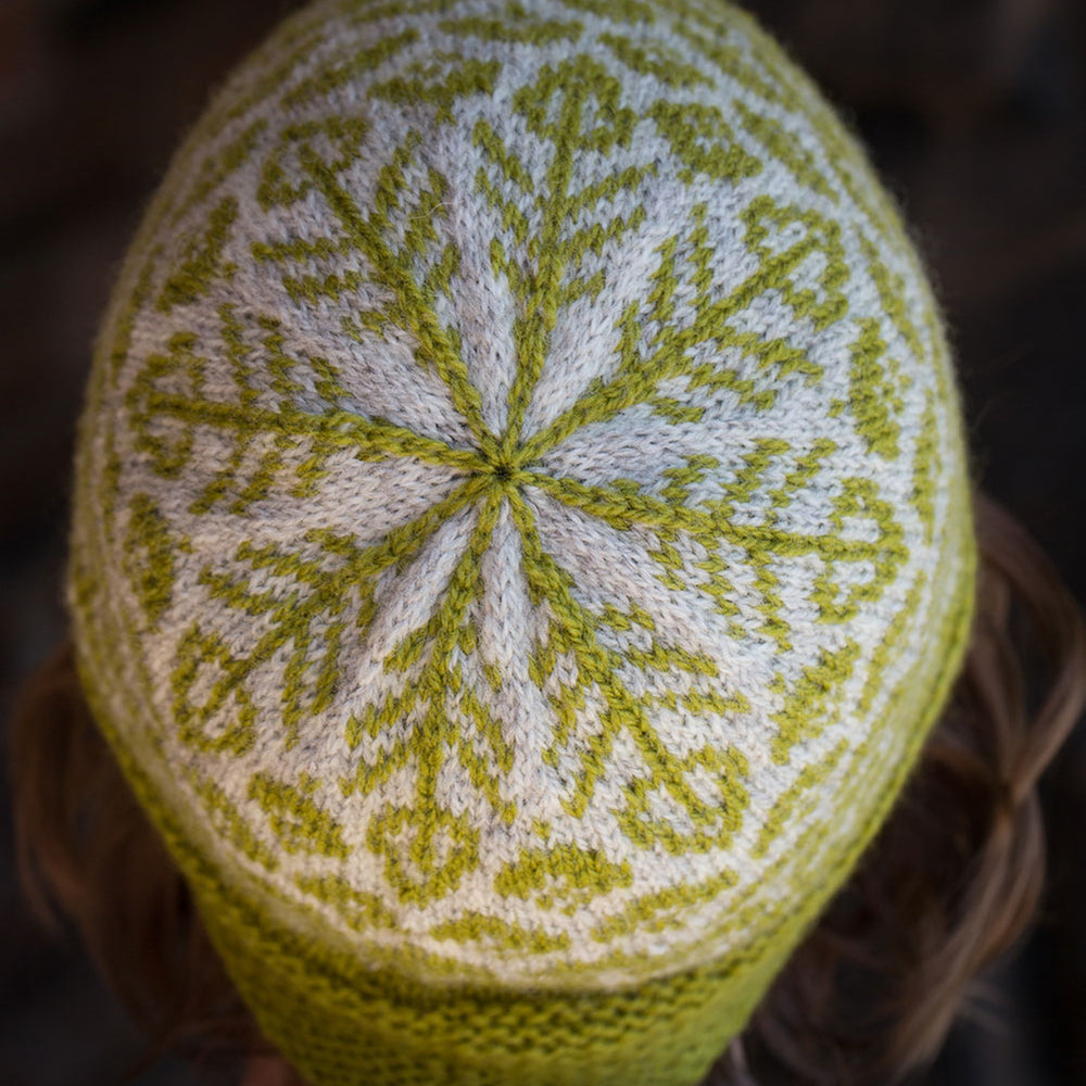 close up of the crown of the hat, in green and grey. The leaf motifs come together like a snowflake in the centre.