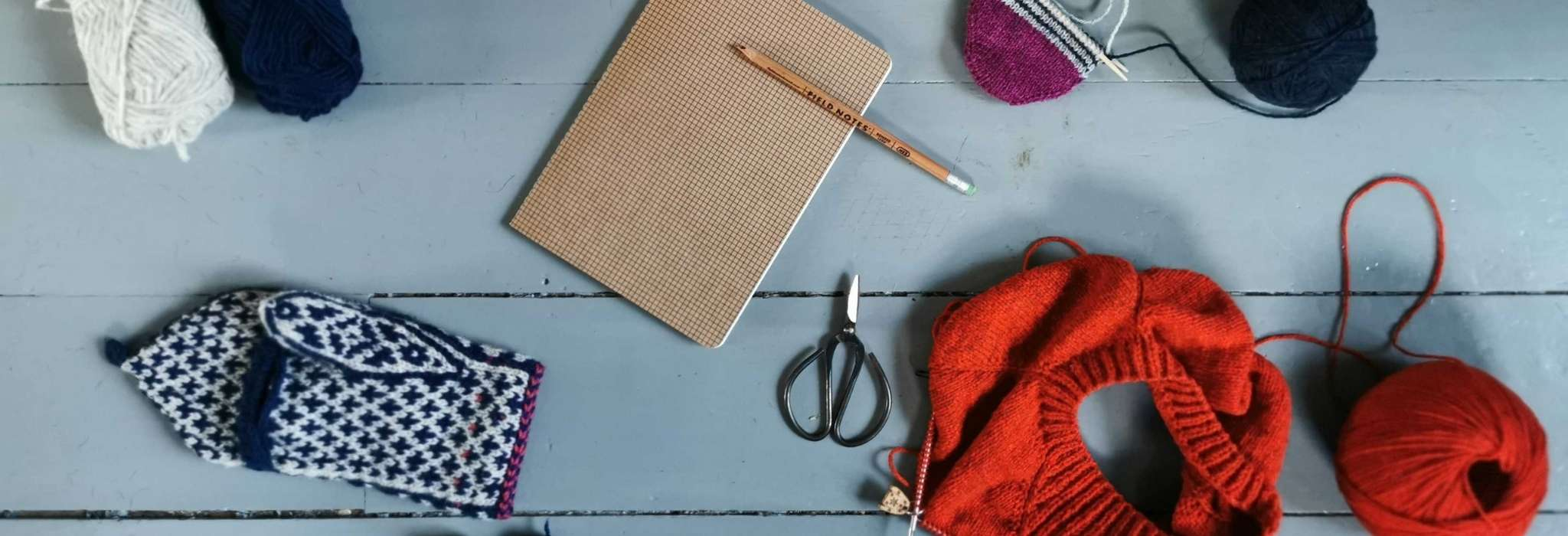 A grey wooden floor with balls of yarn, one unfinished navy and white mitten, a brown notebook and pencil, a small pair of scissors, and an orange sweater in progress next to a ball of orange yarn.