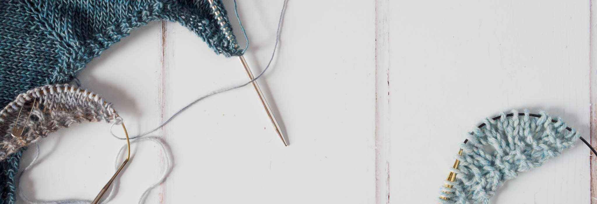 Light blue yarn and blue circular knitting needles on a wooden countertop.