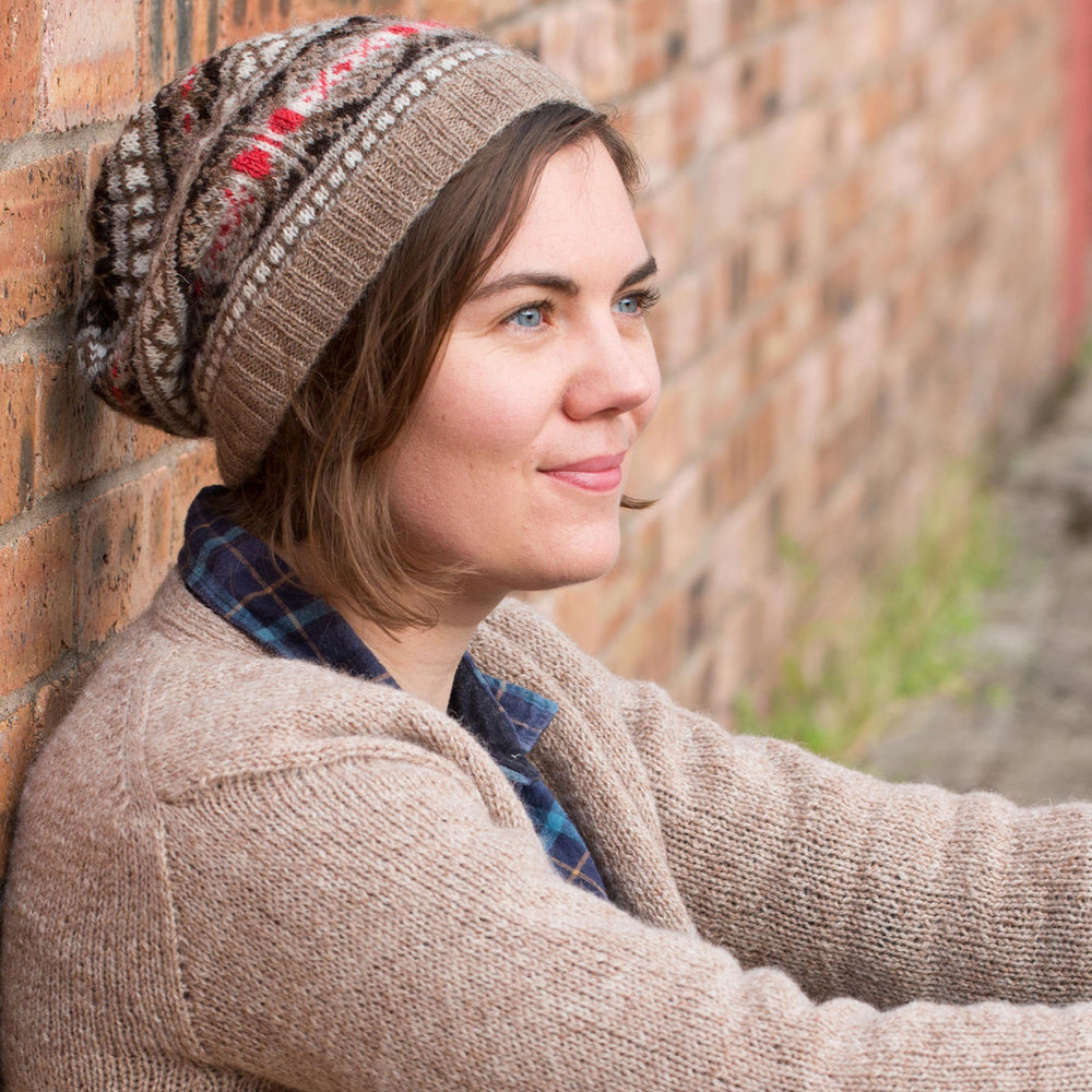 Ysolda, a white woman with chin-length brown hair, sits against a brick wall looking to the side. she is wearing a brown jumper and a brown and red fair isle hat.
