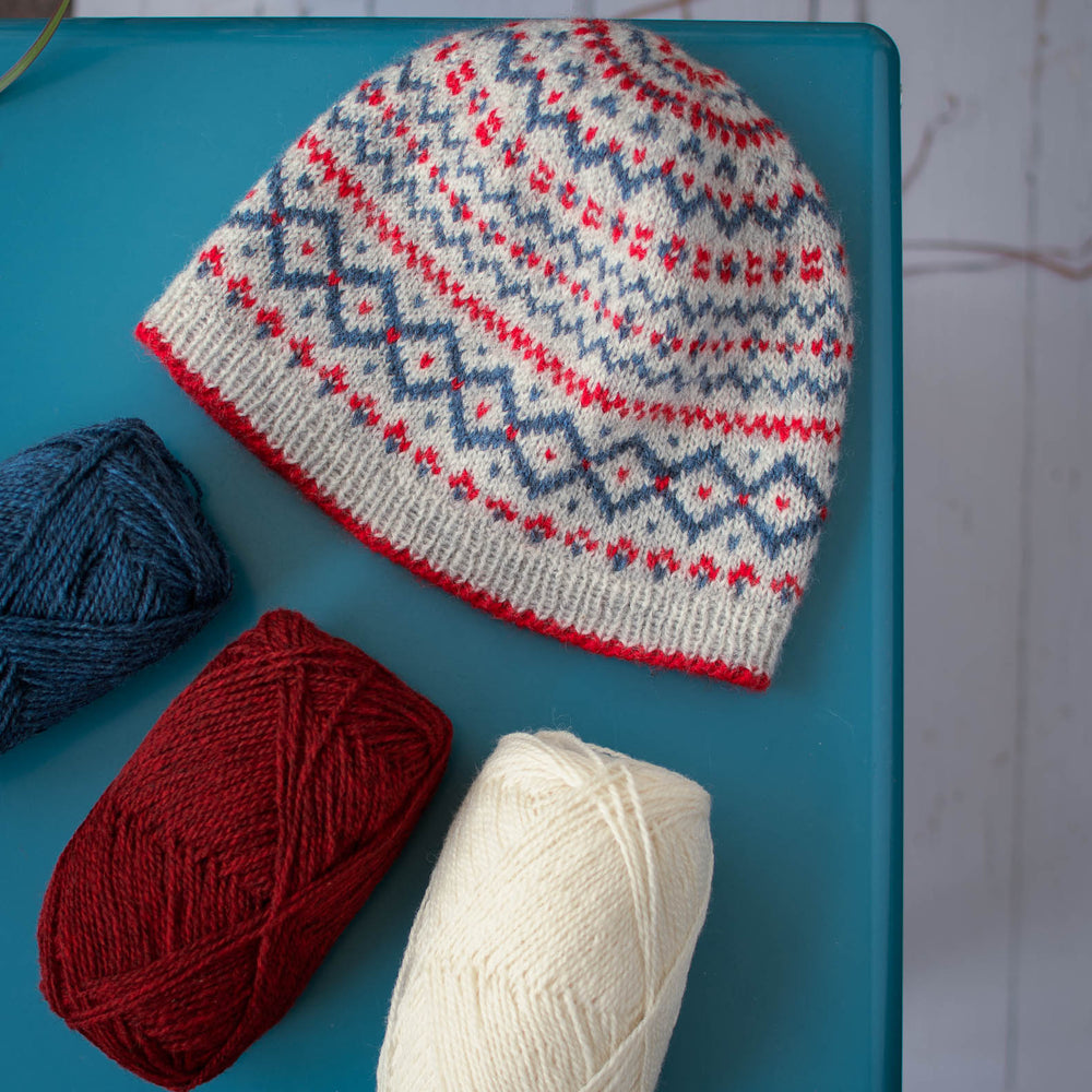 overhead view of stranded colourwork hat and three balls of yarn in red, blue, and white. sitting on a blue table