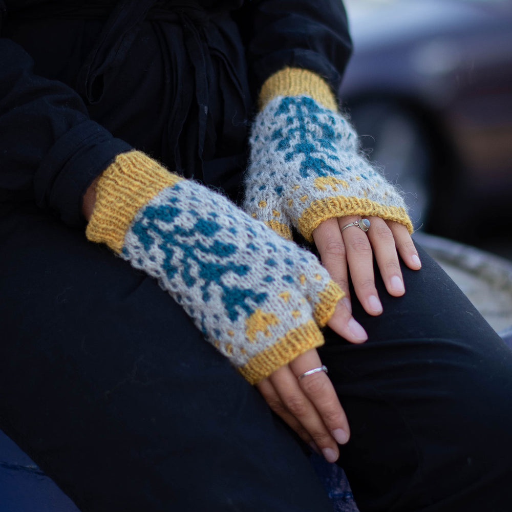 Close up of someone in black with their hands in their lap. They are wearing  bold grey background and blue geometric botanic wool fingerless mitts with yellow trim at the cuff, and fingers.