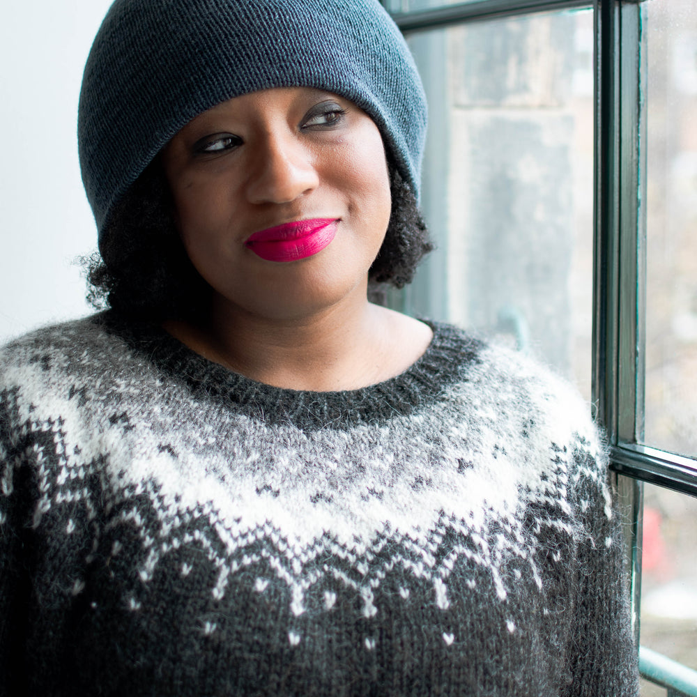 A black woman wearing pink lipstick and a blue beanie stands in front of a window. She's wearing a black wool jumper with an eye catching white, silver, and grey colourwork yoke.
