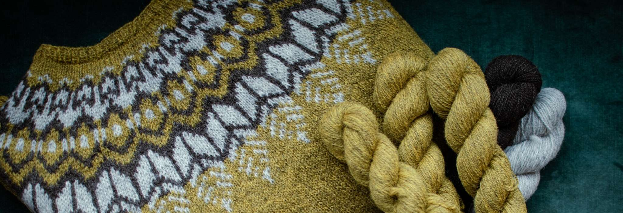 A close up of part of a colourwork yoke sweater in gold, brown and white. Some of the model's dark is visible over the top of the shoulder.