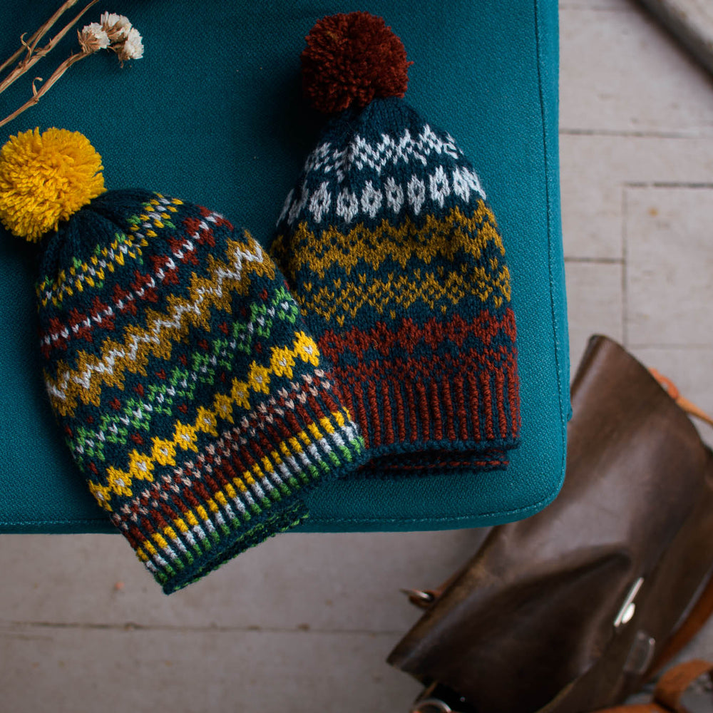 ovehead image of 2 stranded colourwork hats sitting on a blue surface. The hats are a mix of blue, green, yellow, and dark red.