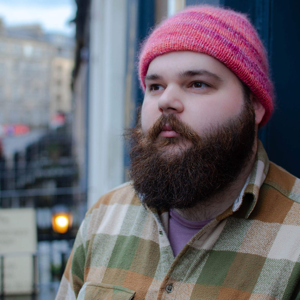 A white man with a bushy brown beard looks up to the right. He is wearing a pink and orange fitted beanie and an orange and green checkered shirt.