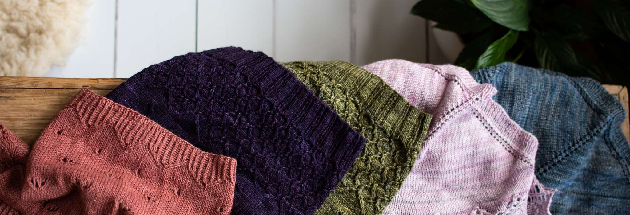 A line up of light weight lacey cowls on a wooden bench