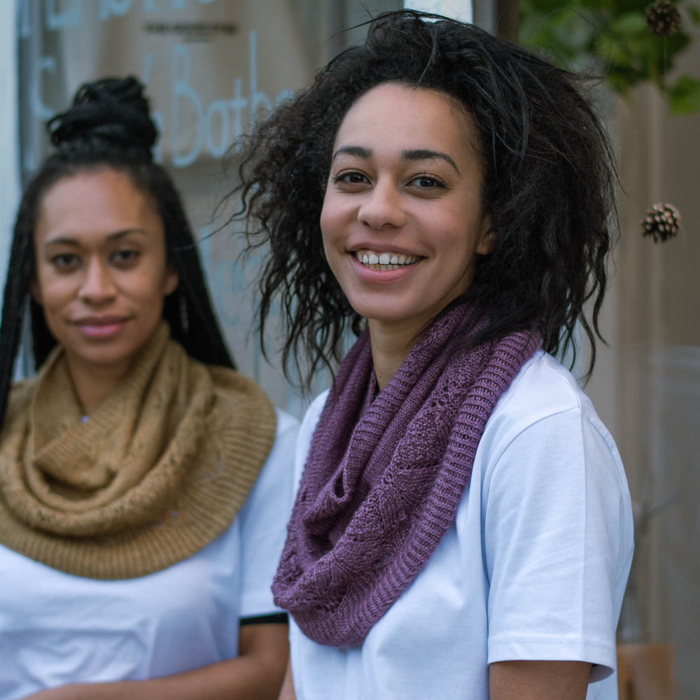 Two black women stand casually in front of a store window. The woman in the foreground has natural hair and she's wearing a deep purple knit cowl and a white t-shirt. Her sister in the back ground has long braids, is wearing a caramel coloured knit cowl over a white t-shirt.