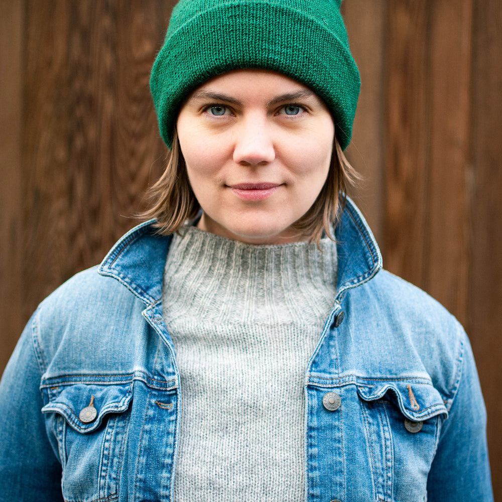 Ysolda, a white woman, stands looking directly at the camera with a small smile. She is wearing a bright green watchcap, grey jumper, and denim jacket