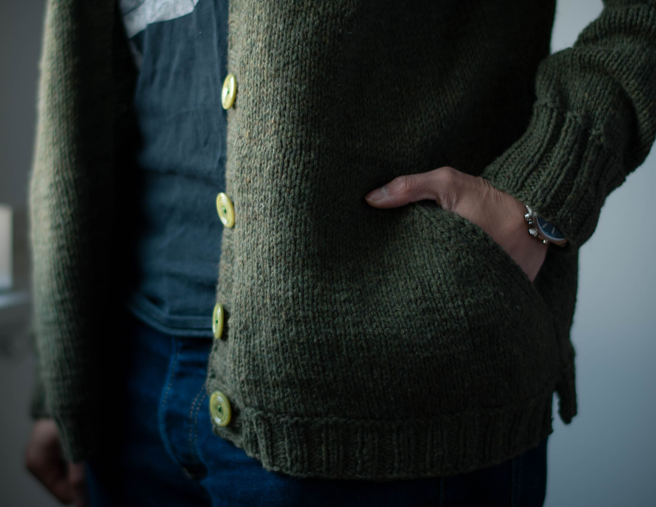 Image of a person wearing an unbuttoned green cardigan, with a brown-skinned hand tucked into the angled pocket.