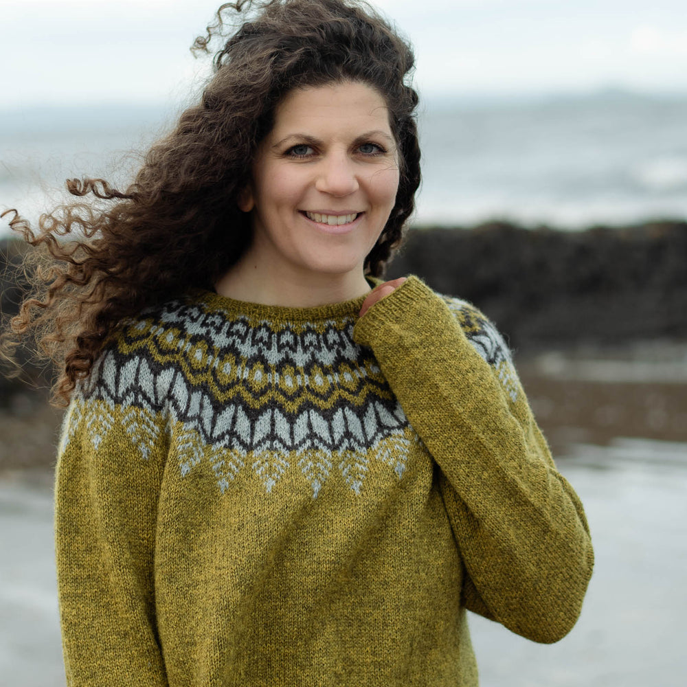 A white woman with long curly brunette hair stands on the beach smiling at the camera with the sea behind her. She is wearing an earthy green knit sweater with a dark brown and light grey colourwork yoke. Her left arm is folded up and her hand is near her neck holding the cuff of her sweater.