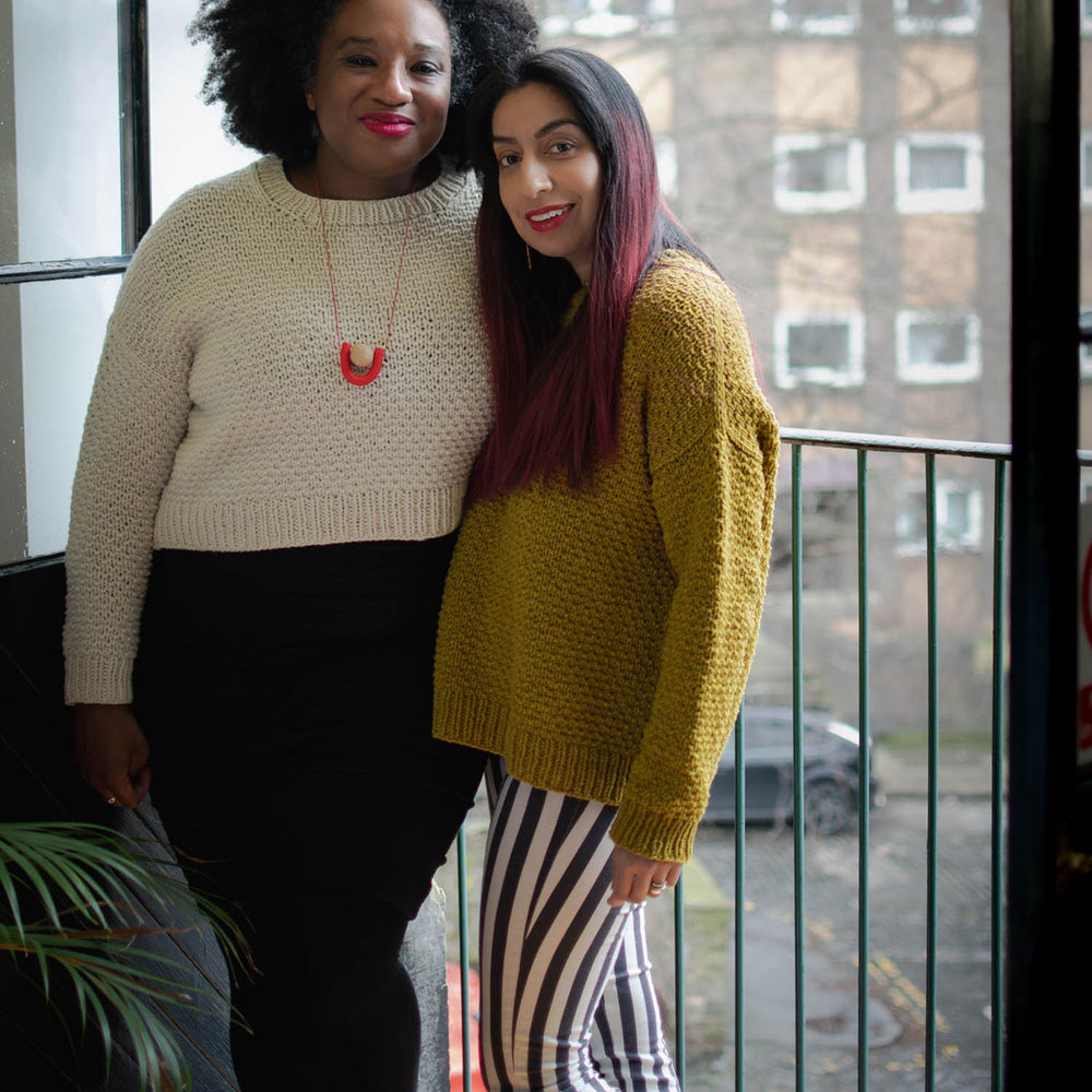 Two women stand in front of an open doorway. To the left the black woman is slightly taller has natural hair and red lipstick. They're wearing a cropped cream textured knit sweater of a black dress, they've got their arm around the south asian woman. The south asian woman has long hair with red highlights worn down over her shoulders. They're wearing a mustard coloured hip length textured jumper over bold black and white stripped trousers.