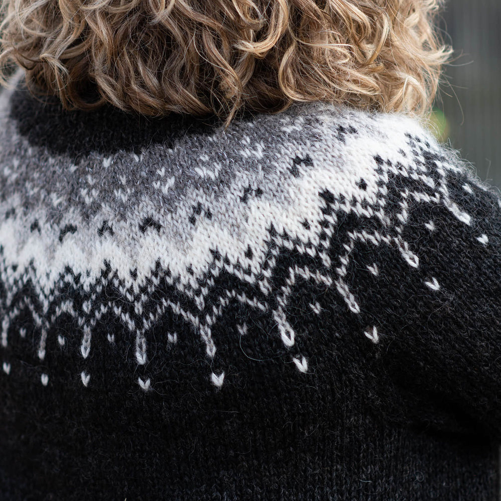 Cropped image of the back yoke of the Bleideag pattern, black sweater with a grey, silver, and white colourwork yoke. The person wearing the sweater has curly shoulder length blond hair.