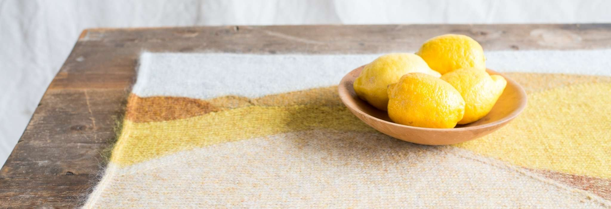 A yellow, orange and white table mat is placed on a wooden table. On top is a small wooden bowl holding four lemons.